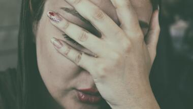 Frau hält sich Hand ins Gesicht