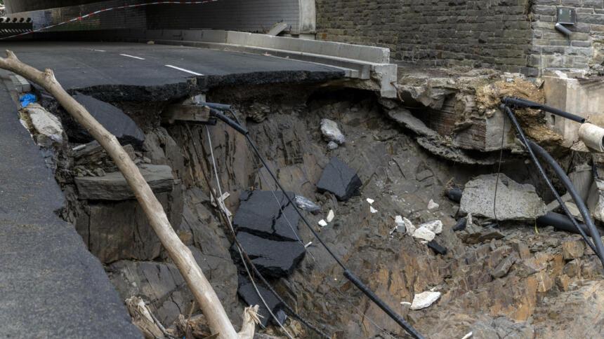 Abbruchkante einer Straße im Ahrtal. Abgerissene Leitungen hängen heraus.