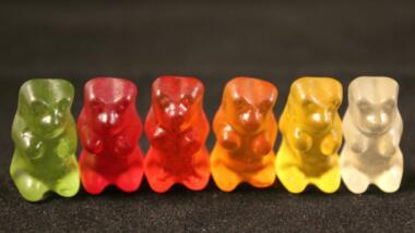 Sechs Gummibärchen in verschiedenen Farben stehen in einer Reihe.
