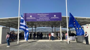 Das Bild zeigt den Eingan des Lagers auf Samos mit einem Schild, davor wehen Fahnen Griechenlands und der EU.
