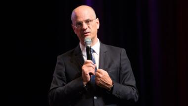 Jean-Michel Blanquer mit einem Mikrofon in der Hand