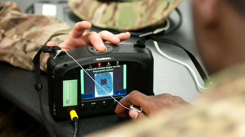 Das Bild zeigt einen Iris- und Fingerabdruckscanner in der Hand von US-Soldat:innen.