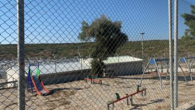 Das Bild zeigt einen eingezäunten Spielplatz, der sich im Lager Samos befindet, mit Wippe und Schaukel.