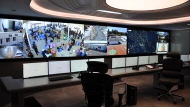 Das Bild zeigt einen Raum mit Monitoren und Leinwand, auf dem mehrere Menschen Bilder aus dem Lager Samos gezeigt werden.