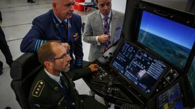 Das Bild zeigt drei Männer beim Steuern einer Drohne an Bildschirmen.
