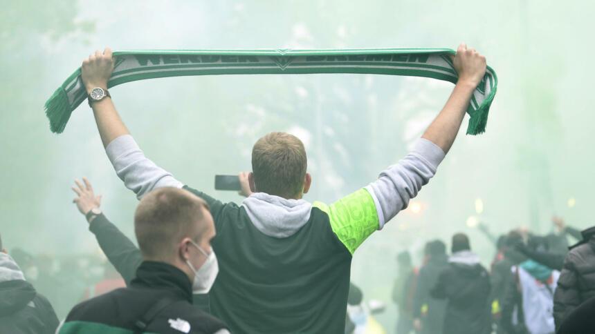 Fan von Werder Bremen steht zwischen anderen grüngekleideten Fans und hält grünen Fanschal hoch. Im Hintergrund grüne Rauchschwaden.