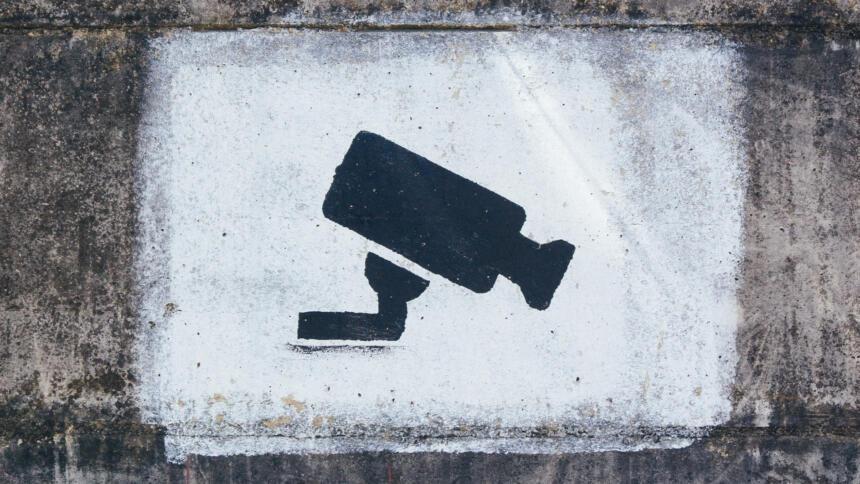 Die Schablone einer Überwachungskamera ist auf eine Wand gesprüht.