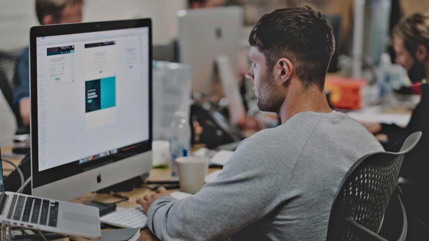 Ein Angestellter sitzt vor einem Computer.
