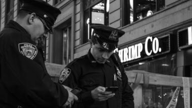 Zwei Polizisten in Uniform schauen auf ihre Smartphones.