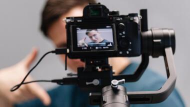 Eine Videokamera ist auf einen Mann gerichtet, der sich selbst filmt.