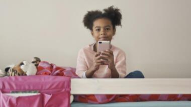 Ein Mädchen sitzt auf einem Bett und hält ein Handy.