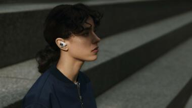 Frau trägt Bluetooth-Kopfhörer
