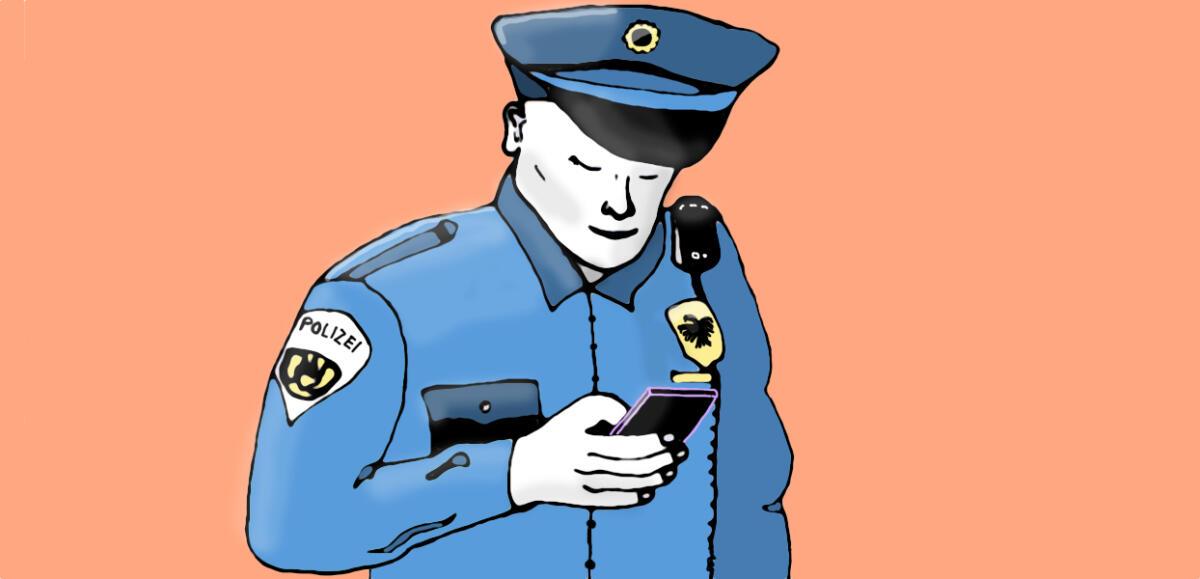 Ein Polizist schaut auf ein Smartphone