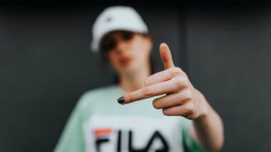 Eine Frau mit Kappe zeigt den Mittelfinger in die Kamera.