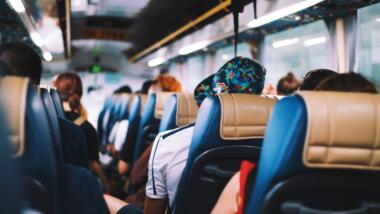 Das Bild zeigt das Innere eines Busses mit Passagieren die von hinten aufgenommen wurden.