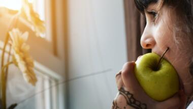 Eine Person beißt in einen Apfel und schaut aus dem Fenster