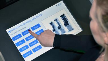 Das Bild zeigt eine Person an einem Selbstbedienungskiosk zur Abgabe von Fingerabdrücken.
