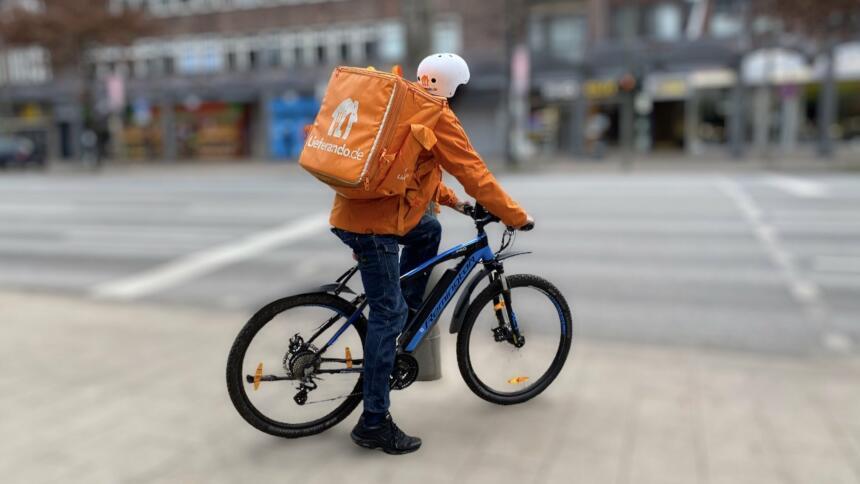 Ein Lieferando-Fahrer auf einem Rad vor einer verschwpommen fotografierten Straße