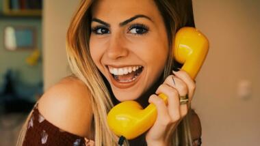Frau an gelben Telefon