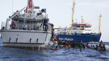 Das Bild zeigt Geflüchtete im Wasser vor einem libyschen Küstenwachschiff, im Hintergrund ein Schiff von Sea-Watch.