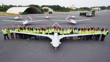 Das Bild zeigt eine Drohne auf einem Rollfeld in Vorderansicht, hinter der sich offenbar Mitarbeiter*innen der Firma Baykar aufreihen, im Hintergrund weitere Drohnen.