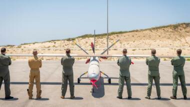 Das Bild zeigt eine Drohne, vor der sechs Soldat:innen mit verschränkten Armen und mit dem Rücken zur Kamera stehen.