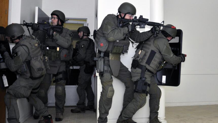 Das Bild zeigt dunkel gekleidete Männer in Uniformen und automatischen waffen, die einen Raum betreten haben und offenbar absichern.