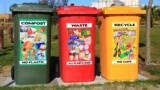 Drei bunte Mülltonnen stehen nebeneinander.