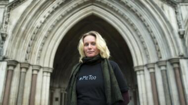 Das Bild zeigt Kate Wilson vor einem verzierten Eingang des Königlichen Gerichts in London.