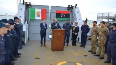 Auf einem libyschen Patrouillenschiff hängen die Fahnen Italiens und Libyens, davor stehen Männer der Küstenwachen, ein Mann hält an einem Podest eine Rede.