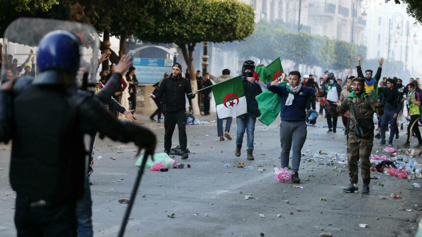 Demonstranten mit Algerienflaggen stehen behelmten Polizisten gegenüber