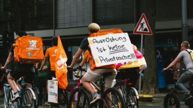 """Demo von Lieferando-Fahrer:innen. Auf dem Demoschild steht: """"Ausrüstung ist keine Privatsache"""""""