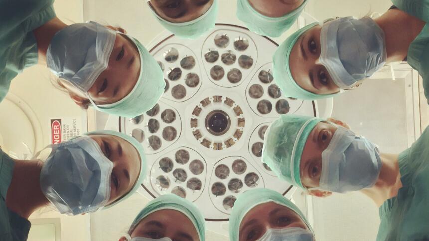 Menschen mit OP-Masken stehen im Kreis und blicken in die Kamera