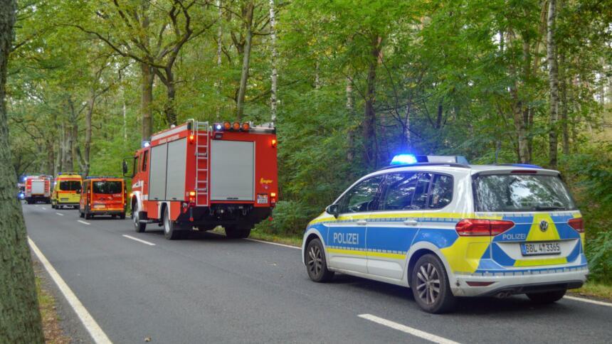 Straße durch einen Wald, befahren von Fahrzeugen der Polizei, der Feuerwehr und des Rettungsdienstes, teilweise mit Blaulicht.