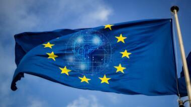 Eine Europafahne vor blauem Himmel. In der Mitte der Fahne lässt sich leicht ein künstliches Gehirn erkennen.