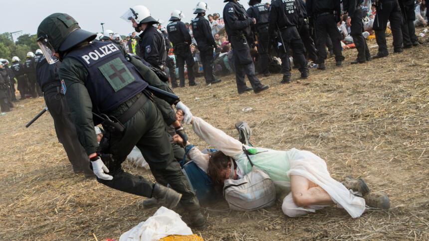 Polizist zerrt Frau über Boden