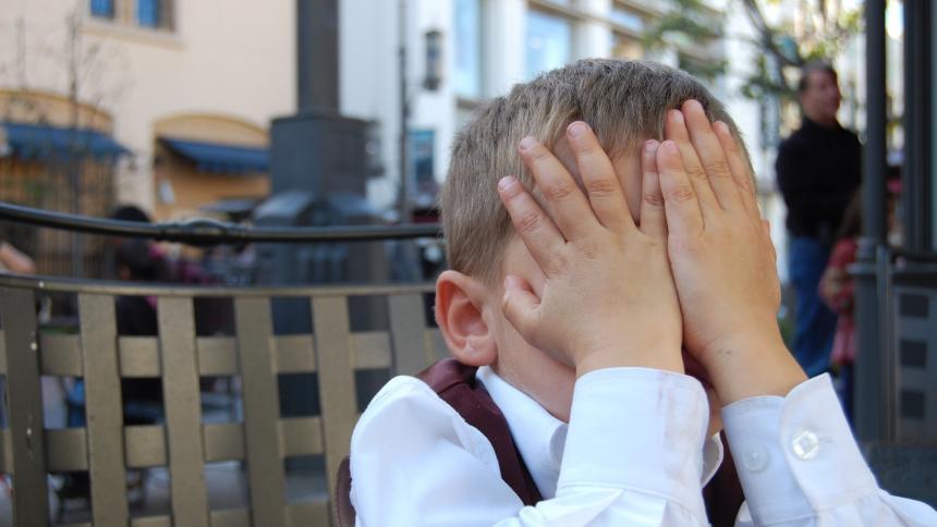 Kind mit Händen vor dem Gesicht